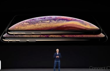 Tim Cook op podium met iPhone Xs.